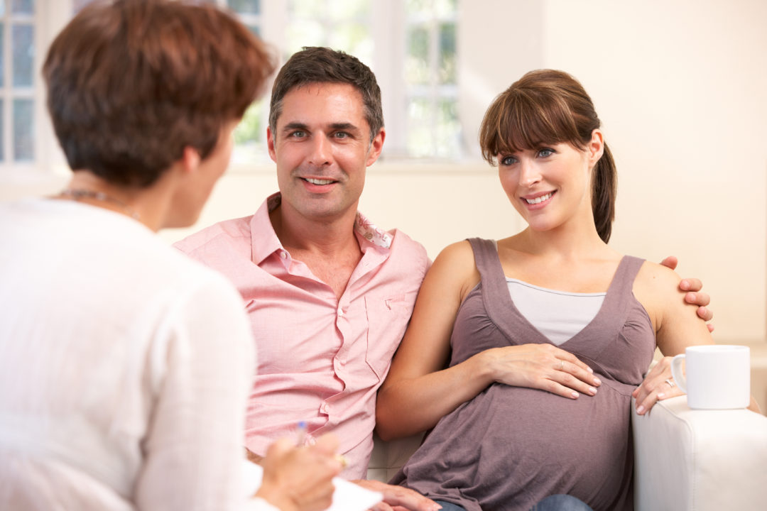 Expectant couple talking to birth mentor